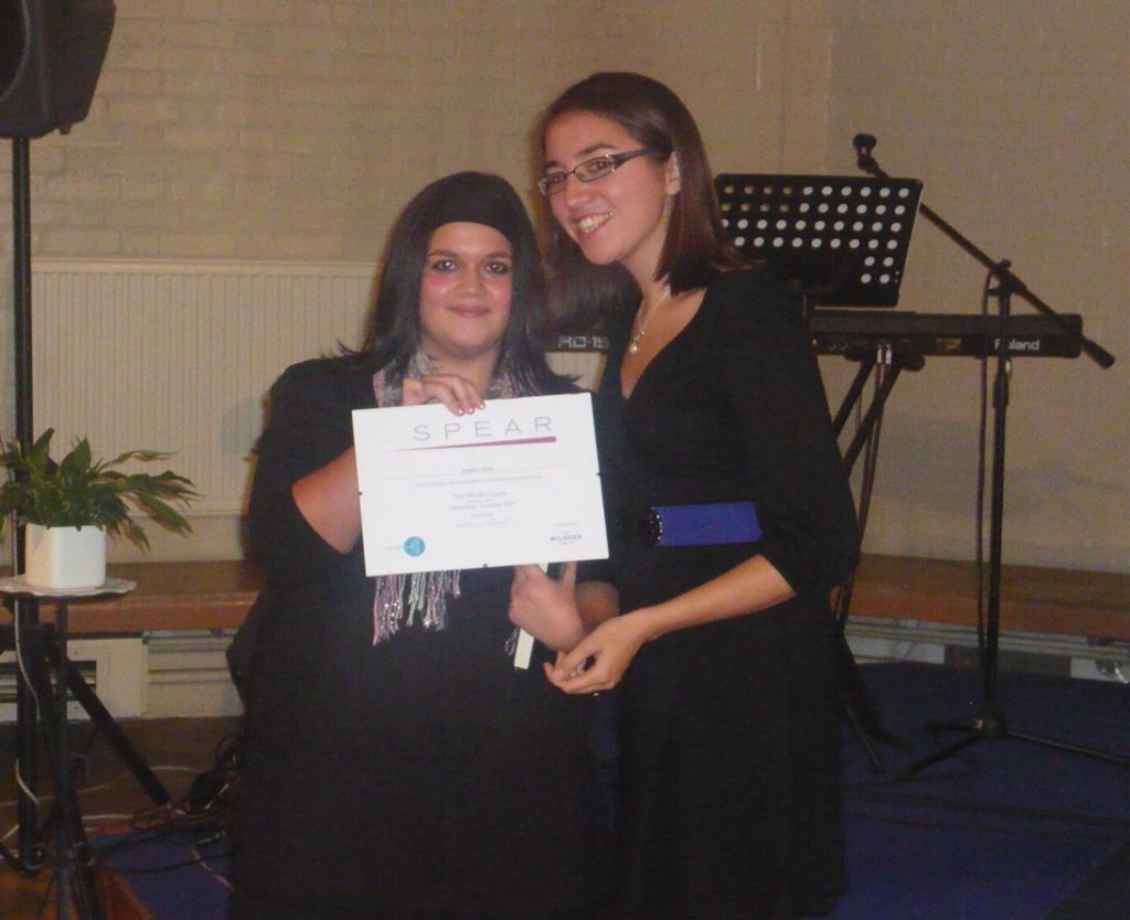 Young person holding certificate with keyboard and music stand in background