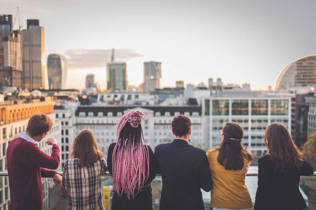 Group of people from behind looking out over city skyline