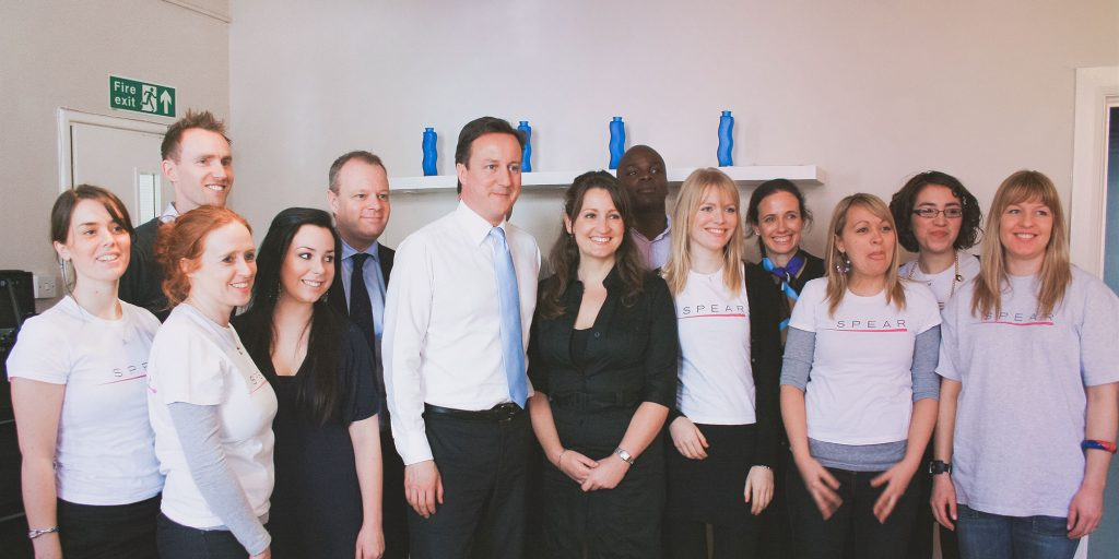 David Cameron in suit smiling with group of people